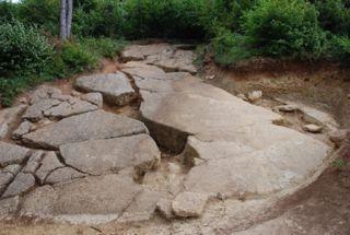 """Abb. 4 Blick auf eine der beiden Probegrabungen am Nordhang. Diese zerborstenen Steinplatten sollen die Überreste der einstigen Pyramide sein, die in """"Kronenbauweise"""" aus Kunstbeton errichtet worden sein sollte. Eine regelmäßige Struktur der Bauelemente war auf unserer Inspektion nicht nachzuweisen."""